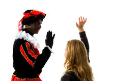 Girl waves goodbye to Zwarte Piet ( black pete). Blonde girl waves goodbye to Zwarte piet ( black pete) typical Dutch character part of a traditional event Royalty Free Stock Image