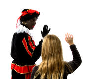 Girl waves goodbye to Zwarte Piet ( black pete). Blonde girl waves goodbye to Zwarte piet ( black pete) typical Dutch character part of a traditional event Stock Photography