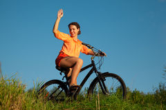 The girl waves a hand sitting on a bicycle Stock Images
