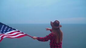 Girl in a cowboy hat with an American flag. America symbol