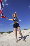 Girl waving Britain flag and fixing her hair Royalty Free Stock Photos