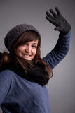 Girl waving at camera with warm hat scarf and gloves Royalty Free Stock Image