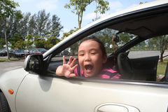 Girl waving in the car. Girl smiling and waving goodbye in the car happily Stock Image