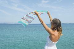 Girl waving a colourfull scarf on seaside Stock Photography