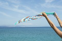 Girl waving a colourfull scarf on seaside Royalty Free Stock Photo