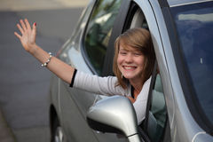 Girl waving goodbye from car. Fourteen year old teenage girl cheering and waving goodbye enthusiastically through an open car window. Focus on eyes, hand Royalty Free Stock Photos