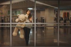 Girl waving goodbye hand. Girl with teddy bear in his hands waving goodbye hand, it is very sad Royalty Free Stock Photography