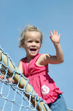 Girl waving hand. A beautiful little caucasian white girl child with blond curly hair and happy laughing expression in her pretty face waving her hand to greet Royalty Free Stock Images