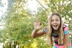 Girl waving hello Royalty Free Stock Image