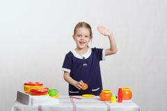 Girl waving a toy kitchen Royalty Free Stock Image