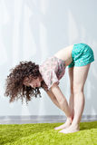 Girl with wavy hair doing yoga in the morning in the room. Royalty Free Stock Image