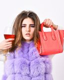 Girl wear fashion fur vest while posing with bag. Luxury store concept. Lady likes shopping. Woman with handbag hold. Glass of wine. Elite fashion clothes stock photos