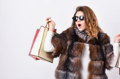 Girl wear sunglasses and fur coat shopping white background. Lady hold shopping bags. Discount and sale. Buy with. Discount on black friday. Shopping with promo stock photos