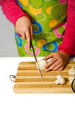 Girl wearing apron slicing mushrooms Royalty Free Stock Photos
