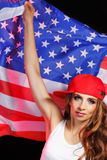 Girl wearing a baseball cap holding a US flag Royalty Free Stock Photography