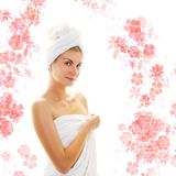 Girl wearing bath towels. Beautiful girl wearing bath towels and flowers around her Royalty Free Stock Photos