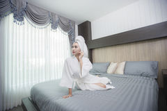 The girl wearing a bathrobe in the bedroom. Stock Images