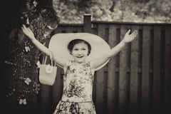 Girl Wearing a Big Sun Hat with Hands Up - Vintage stock image