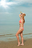 Girl wearing bikini and hat. On toes toward the sun at the sandy beach royalty free stock images