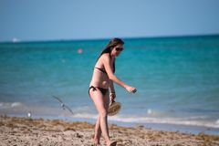 Girl wearing bikini missing the ball playing paddleball on the b royalty free stock photography