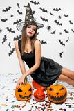 Girl wearing black dress, witch hat and high heels sits on the pumpkin. Halloween pumpkins are next to her stock photography