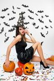 Girl wearing black dress, witch hat and high heels sits on the pumpkin. Halloween pumpkins are next to her royalty free stock images