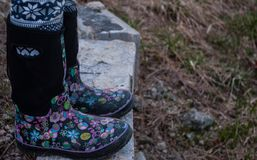 Girl wearing black rubber boots with pink designs royalty free stock images