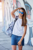 Girl wearing blank white t-shirt, jeans posing against rough street wall. Hipster girl wearing blank white t-shirt, jeans and sunglasses posing against rough Royalty Free Stock Image