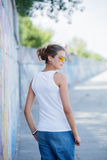Girl wearing blank white t-shirt, jeans posing against rough street wall Stock Photos