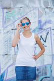 Girl wearing blank white t-shirt, jeans posing against rough street wall. Hipster girl wearing blank white t-shirt, jeans and sunglasses posing against rough royalty free stock photography