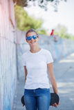 Girl wearing blank white t-shirt, jeans posing against rough street wall