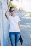 Girl wearing blank white t-shirt, jeans posing against rough street wall. Hipster girl wearing blank white t-shirt, jeans and sunglasses posing against rough Stock Photo