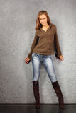 Girl wearing blouse and boots stand near wall Stock Photo