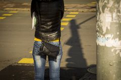 A girl wearing blue jeans standing on a walkway. her blouse is in the exact color of the pedestrian path. A weak woman in jeans and a black leather jacket Royalty Free Stock Photography