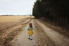 Girl Wearing Blue Long-sleeved Shirt and Yellow Skirt Walking on Pathway Stock Photos