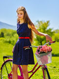 Girl wearing blue sundress rides bicycle with flowers basket. Royalty Free Stock Photography