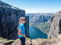 Norway - Girl in blue T-shirt and a fjord view. Girl wearing blue T-shirt looks up, on the surrounding cliffs. She is enjoying the fjord view in front of her royalty free stock photo