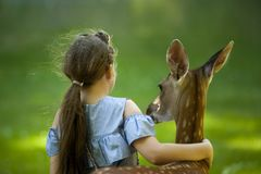Girl Wearing Blue Top With her hand around a deer stock photography