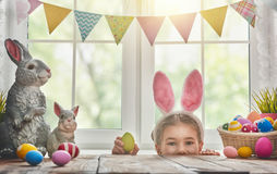 Girl wearing bunny ears. Happy Easter! Cute little child girl wearing bunny ears on Easter day. Child girl laughs and enjoys spring and a holiday stock photo