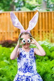 Girl Wearing Bunny Ears and Silly Egg Eyes. A funny portrait of a girl having fun on Easter wearing bunny ears and holding up silly eyes made from eggs outside Royalty Free Stock Photos