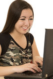 Girl wearing camouflage tee shirt typing on computer Royalty Free Stock Image