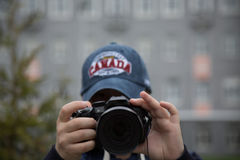Girl wearing cap Canada taking pictures street Stock Photo