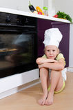 Girl Wearing Chef Hat Waiting Beside Oven for Food Stock Images