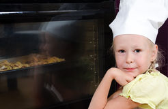 Girl Wearing Chef Hat Waiting Beside Oven for Food Royalty Free Stock Photo