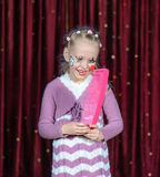 Girl Wearing Clown Make Up Holding Over Sized Comb Stock Image