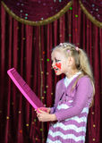 Girl Wearing Clown Make Up Holding Over Sized Comb Stock Photo