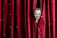 Girl Wearing Clown Makeup Peeking Through Curtains. Young Blond Girl with Face Painted in Clown Make Up Smiling and Peeking Out Through Opening in Red Stage stock photo