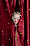 Girl Wearing Clown Makeup Peeking Through Curtains. Young Blond Girl with Face Painted in Clown Make Up Smiling and Peeking Out Through Opening in Red Stage royalty free stock images