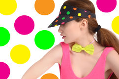 Girl wearing a colorful polka dotted visor and a neon green bowtie. Stock Photography
