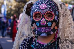 Girl wearing colorful skull mask and lace veil for Dia de Los Muertos/Day of the Dead. Celebration Stock Photos
